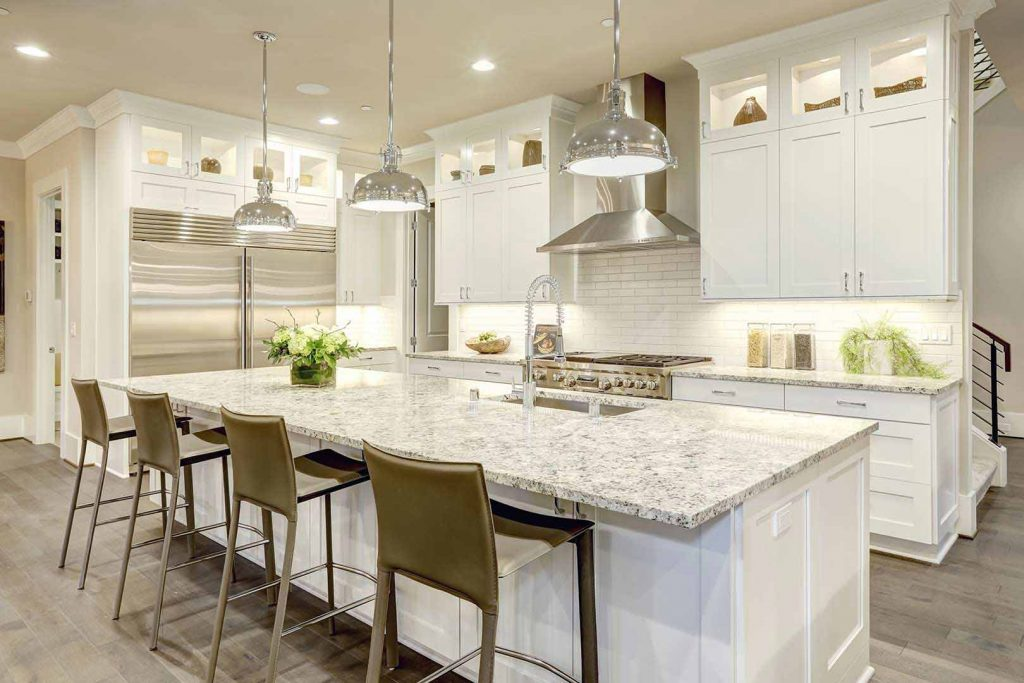 Kitchen with large white island with granite top